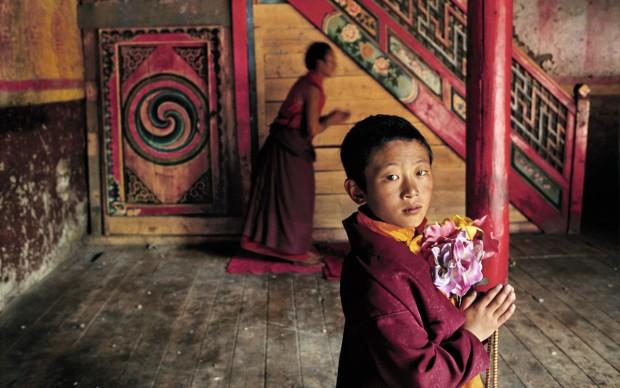 Steve McCurry - Giovane monaco con fiori, Larung Gar, Kham, Tibet, 2000 © St. Moritz Art Masters 2013