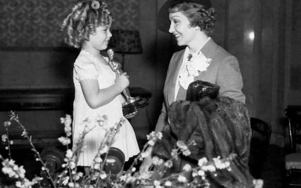 Claudette Colbert riceve l'Oscar dalle mani di Shirley Temple