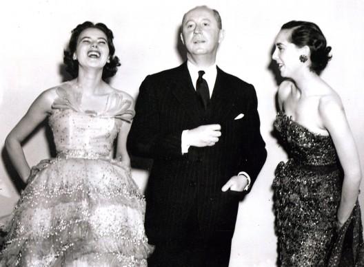 Christian Dior in compagnia di due modelle, che indossano entrambe una sua creazione.