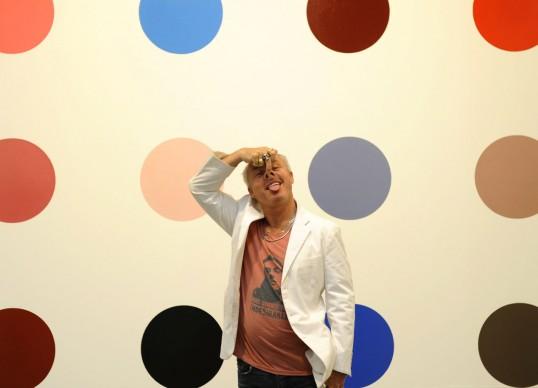 Damien Hirst posa di fronte alla sua opera Minoxidil, 2005 presso la sede di New York della Gagosian Gallery nel 2012, in occasione dell'anteprima stampa della mostra The Complete Spot Paintings 1986-2011. Credits: TIMOTHY A. CLARY/AFP/Getty Images