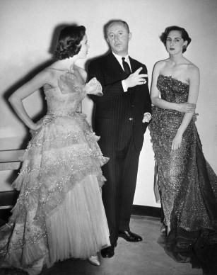 Christian Dior in compagnia di due modelle, che indossano entrambe una sua creazione. Credits: Keystone/Getty Images
