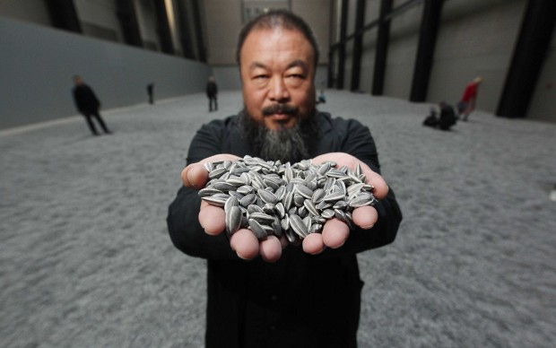 """Ai Weiwei mostra alcuni dei """"Sunflower Seeds"""" in porcellana che compongono l'omonima installazione in mostra alla Tate Modern di Londra, dall'ottobre del 2010 a maggio 2011 (Photo by Peter Macdiarmid/Getty Images)"""