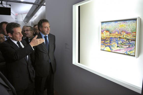 L'allora Presidente della Francia, Nicolas Sarkozy, davanti al dipinto di Georges Braque 'Le canal Saint-Martin' in mostra al Pompidou Mobile nell'ottobre del 2011 (Photo by PHILIPPE WOJAZER/AFP/Getty Images)