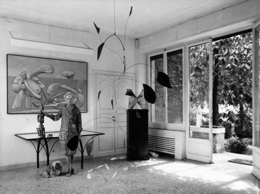 Peggy Guggenheim nell'ingresso della sua residenza di Venezia. Appesa al soffitto, una scultura di Alexander Calder del 1941, mentre alle spalle della collezionista si vede un dipinto di Picasso del 1937 (Photo by Keystone/Getty Images)