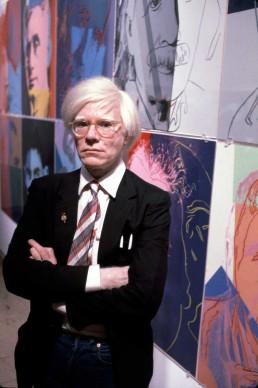 Andy Warhol e una serie di suoi dipinti, negli anni Ottanta (Photo by Susan Greenwood / Liaison Agency)