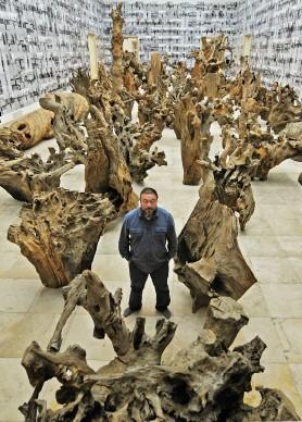 Ai Weiwei posa nel mezzo dell'installazione Rooted Upon, presso la Haus der Kunst di Monaco, nell'ottobre del 2009 (Photo by JOERG KOCH/AFP/Getty Images)