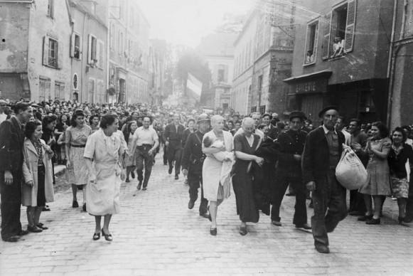 Una donna, il cui bambino è nato da una relazione con un tedesco, e sua madre vengono pubblicamente umiliate per le strade di Chartres, accusate di collaborazionismo con le truppe naziste (Photo by Robert Capa/Getty Images)