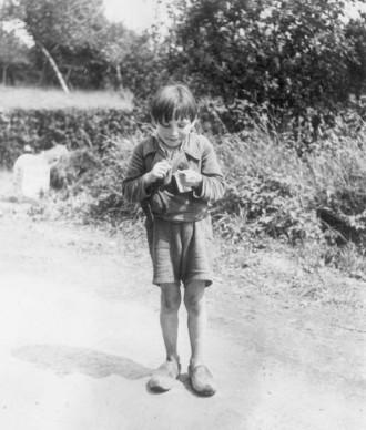 Robert Capa, Un ragazzo francese mangia della cioccolata donatagli da alcuni soldati statunitensi, 1944  (Photo by Robert Capa/Keystone/Getty Images)