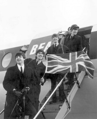 I Beatles sventolano la 'Union Jack', bandiera del Regno Unito, mentre salgono su un aereo a Londra, nel 1964  (Photo by Evening Standard/Getty Images)