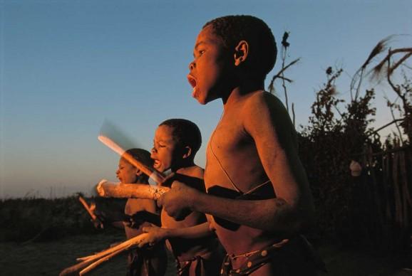 Chris Johns, Lukulu - Zambia, 1996. Ragazzi della tribù Luvale salutano l'alba con canti e percussioni tradizionali nel villaggio di Lukulu, lungo il tratto superiore dello Zambesi. Il fotografo, Chris Johns, è diventato direttore del magazine americano nel 2005.
