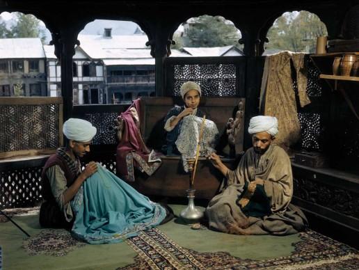 Volkmar Wentzel, India, 1947. Su un terrazzo coperto affacciato sulla valle del Kashmir, tessitori di seta di Srinagar fumano una pipa ad acqua mentre lavorano.