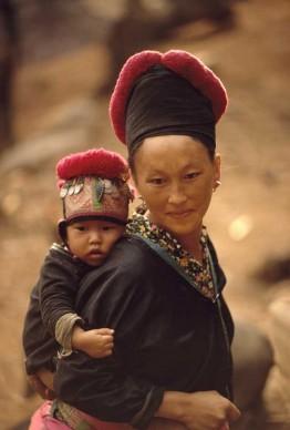 W.E. GARRETT, Laos, 1974. Una donna hmong e suo figlio con il copricapo tradizionale.