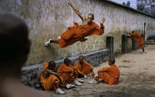 Steve McCurry - Un giovane monaco corre lungo un muro sopra i suoi compagni. Shaolin Monastery, Hunan Province, China; 2004