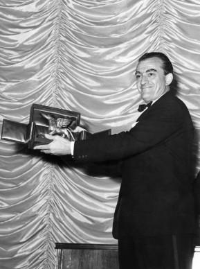 Luchino Visconti mostra il Leone d'Argento, vinto nel settembre del 1957 alla 18esima Mostra Internazionale del Cinema di Venezia (Photo credit should read STAFF/AFP/Getty Images)