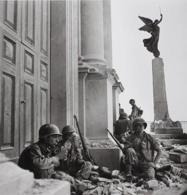 Soldati americani a Troina, nei pressi della cattedrale di Maria Santissima Assunta, dopo il 6 agosto 1943. Photograph by Robert Capa. © International Center of Photography/Magnum – Collection of the Hungarian National Museum