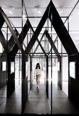 """SET Architects, ALBUM """"Bff016"""", Flagship store Florim © Simone Bossi  L'installazione, collocata in prossimità delle  vetrine dello store, stimola e attira il visitatore permettendo una circolazione fluida all'interno dello spazio. Le quinte, generate dalla struttura autoportante in acciaio e dai teli di iuta, consentono  molteplici  percorsi e modi di  interagire con lo  spazio."""