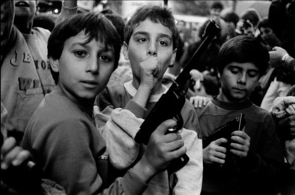 Letizia Battaglia, Festa del giorno dei morti. I bambini giocano con le armi, Palermo, 1986. Courtesy l'artista