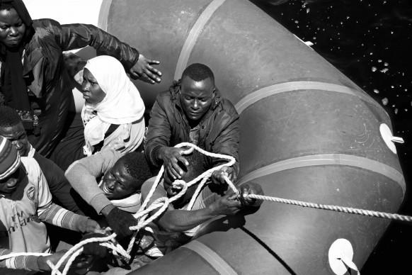 Migranti africani su un gommone, durante le operazioni di salvataggio di Medici senza Frontiere. Dopo essere stati tratti in salvo, i profughi vengono trasferiti via mare su una nave della guardia costiera italiana e condotti in Italia. 26 luglio 2015. © Paolo Pellegrin/Magnum Photos