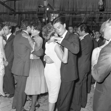"""Foto di Marcello Geppetti, Alain Delon e Romy Schneider ballano durante la serata di premiazione del Ciak d'Oro al ristorante """"Brigadoon"""". Roma, 29 luglio 1961 © MGMC/dolceVita GALLERY"""
