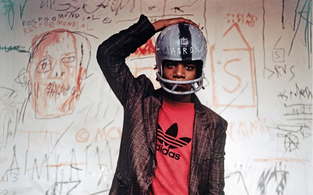 Jean-Michel Basquiat wearing an American football helmet, 1981. Photo: © Edo Bertoglio, courtesy of Maripol. Artwork: © The Estate of Jean-Michel Basquiat. Licensed by Artestar, New York