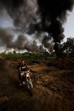 """George Osodi, Smoking Pipe, 2007, dalla serie   """"Oil Rich Niger Delta""""  © l'artista"""