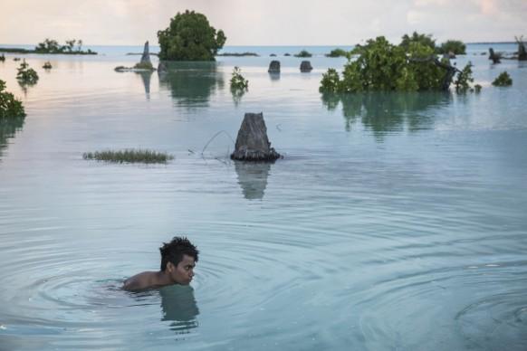 Peia Kararaua, 16 anni, nuota nella zona colpita da una violenta alluvione del villaggio di Aberao sull'atollo di Tarawa nel Kiribati, nell'Oceano Pacifco, 2014 © Vlad Sokhin