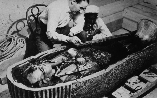 Howard Carter and an Egyptian workman examine the third coffin of Tutankhamun made of solid gold, inside the case of the second coffin. October 1925. Photographed by Harry Burton. INTERFOTO / Alamy Stock Photo