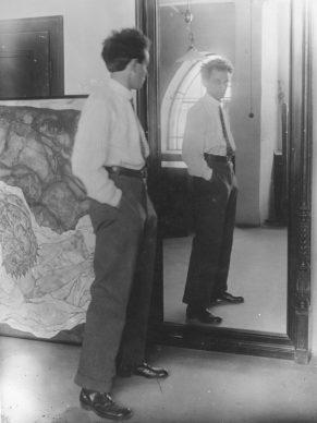 """Ritratto di Egon Schiele del 1915 nel suo Hietzing Atelier, sullo sfondo il dipinto """"Death and Girl"""" © Leopold Privatsammlung/Foto: Leopold Museum, Vienna"""