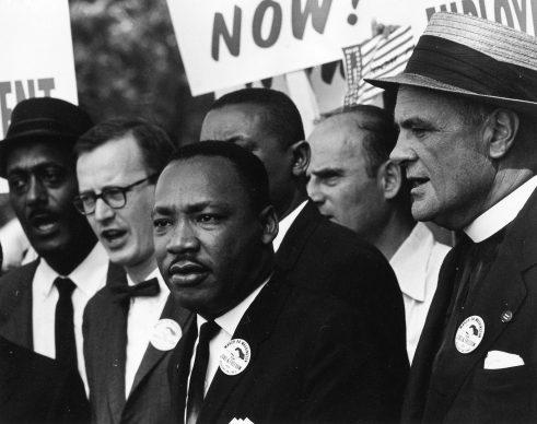 """Martin Luther King Jr. e Mathew Ahmann in mezzo alla folla durante la Marcia per i Diritti Civili͟. È in questa occasione che è stato pronunciato da Martin Luther King, davanti al Lincoln Memorial, il suo più famoso discorso dal titolo """"I have a dream͟"""". 28 agosto 1963, Washington, D.C., USA. Foto di Rowland Scherman (1937) © Courtesy U.S. Information Agency - Press and Publications Service / NARA - National Archives and Records Administration"""