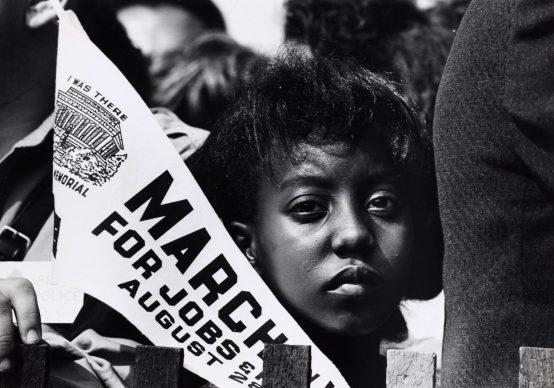 Fotografia di una giovane donna alla Marcia per i diritti civili a Washington, con uno stendardo. 28 agosto 1963, Washington, D.C., USA. Autore sconosciuto © Courtesy U.S. Information Agency - Press and Publications Service / NARA - National Archives and Records Administration