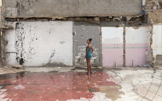 """Teresa Margoles Pista de baile de la discoteca """"Tlaquepaque"""" (Pista da ballo della discoteca""""Tlaquepaque""""), 2016Stampa su carta cotoneProstituta transessuale in piedi sul pavimento della pista da ballo del club demolito a Ciudad Juárez, Mexico45x64,5 cm, con corniceCourtesy dell'artista"""