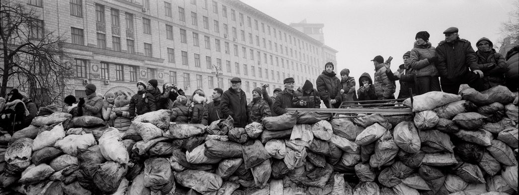 Pavel Wolberg, Ukrainian civilians stand behind a barricade as they watch riot police lines near the Maidan square in Kiev, 2014. Series: Barricades, 2009–14 © Pavel Wolberg, Prix Pictet 2017