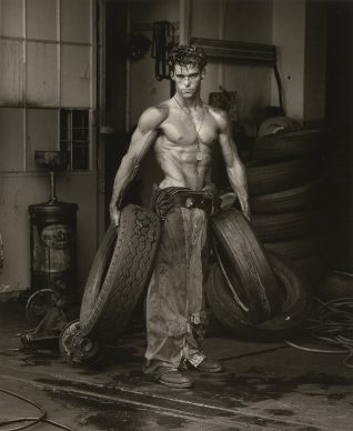 Herb Ritts, Fred with Tires, Hollywood [Body Shop series], 1984. Copyright: © Herb Ritts Foundation. Object Credit: The J. Paul Getty Museum, Los Angeles. Gift of Herb Ritts Foundation
