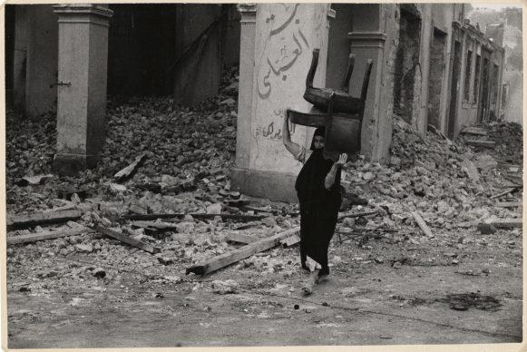 Vrouw loopt door het puin met een stoel op haar hoofd, Port Said, Egypte, november 1956 © Chim (David Seymour),  Magnum  Photos. Courtesy Chim  Estate