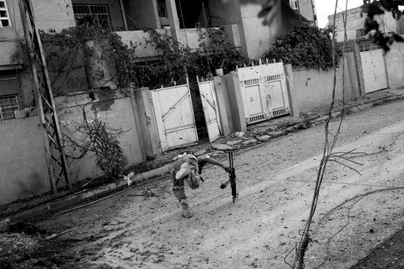 Paolo Pellegrin, Soldiers of the 9th Iraqi armoured division engage with ISIS militants in the Entesar neighborhood in the  eastern side of the city of Mosul. Iraq 2016 © PAOLO PELLEGRIN/MAGNUM PHOTOS