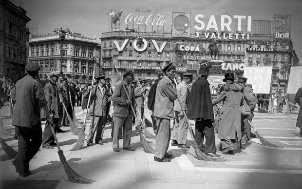 Comparse che interpretano degli spazzini fotografate in Piazza del Duomo durante la lavorazione di una scena del film Miracolo a Milano di Vittorio De Sica, 1951; ©ArchiviFarabola
