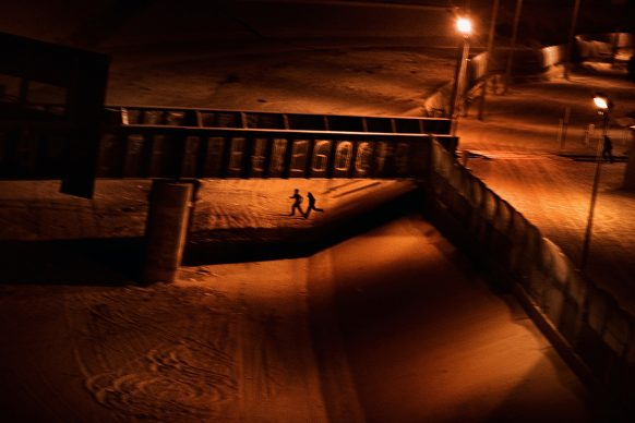 Paolo Pellegrin, Two men who attempted to enter the U.S. illegally run across the dry Rio Grande riverbed back to Ciudad Juárez, Mexico, after being spotted by the U.S. Border Patrol. El Paso, Texas. USA 2011 © PAOLO PELLEGRIN/MAGNUM PHOTOS