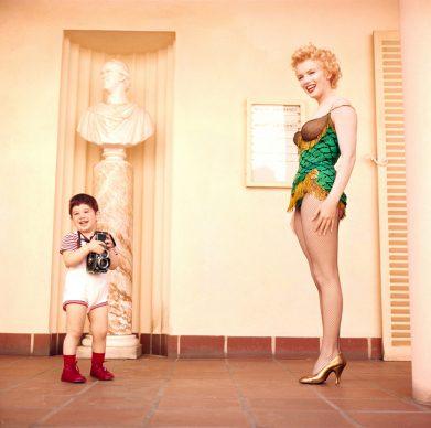 Il figlio del fotografo Milton H. Greene, Joshua, con al collo la macchina fotografica, gioca con Marilyn Monroe durante il servizio pubblicitario realizzato dal padre per il film Fermata d'autobus. Foto di Milton H. Greene © 2018 Joshua Greene archiveimages.com