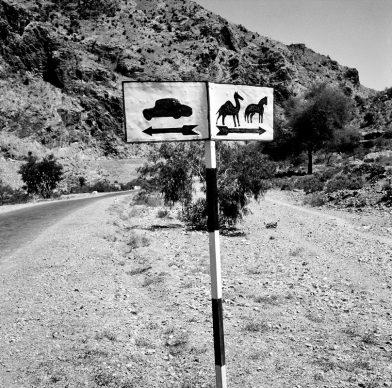 Cartello stradale vicino al Passo di Khyber dove passerà l'Autostrada Asiatica Internazionale, un progetto avviato nel 1958 dall'ONU che mira a modernizzare e collegare le strade esistenti in Asia in una rete di autostrade lunga 34.000 miglia. Aprile 1964, Passo di Khyber, Afghanistan © courtesy UN Photo/WT