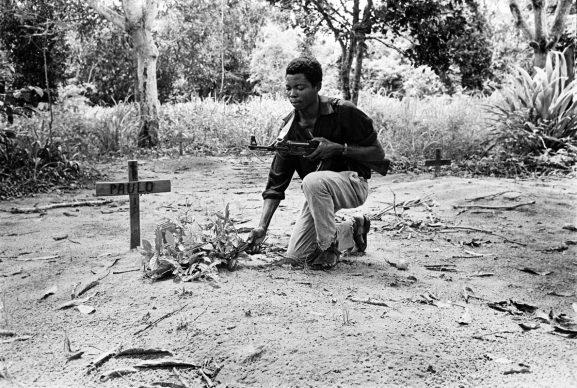 Un guerrigliero del Frelimo, il movimento di liberazione del Mozambico, sulla tomba di un compagno d'armi, provincia di Cabo Delgado, Mozambique, 1972 © courtesy UN Photo/N Basom