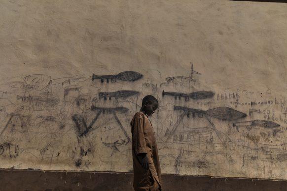 Marco Gualazzini/Contrasto, Un orfano, probabilmente un rifugiato nigeriano, cammina accanto a un muro sul quale sono stati disegnati dei razzi lanciagranate, a Bol, nel Ciad, ottobre 2018. World Press Photo of the Year - Shortlisted