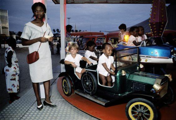 """Bruno Barbey, Car ride at a children's amusement park during the """"Fete de la Renovation"""" at Libreville, 1984 © Bruno Barbey/Magnum Photos, Paris"""