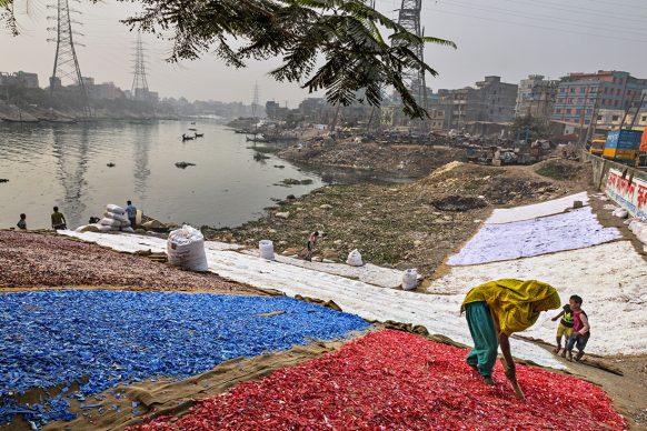 Frammenti di plastica colorata – raccolti, lavati e suddivisi a mano – vengono messi ad asciugare sulle rive del Buriganda. A Dhaka e dintorni sono circa 120.000 le persone che lavorano in questa industria del riciclaggio non ufficiale. I 18 milioni di abitanti di quest'area generano circa 1.000 tonnellate di rifiuti al giorno.  FOTO: Randy Olson/National Geographic