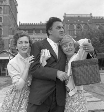 Valentina Cortese ritratta a braccetto con Federico Fellini, abbracciato sull'altro lato dalla moglie Giulietta Masina, di fronte all'hotel Excelsior sul lido di Venezia, nel 1955. (Photo by Archivio Cameraphoto Epoche/Getty Images)