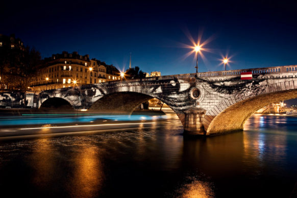 JR, 28 Millimètres, Women Are Heroes, Exhibition in Paris, Pont Louis-Philippe–Pont Marie Side by Night, with Barge, France, 2009. Color lithograph. © JR-ART.NET