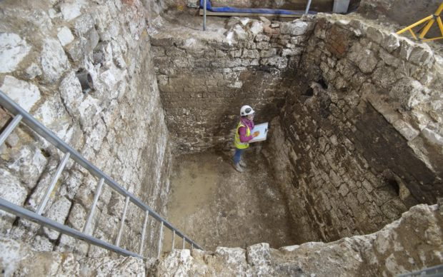 A MOLA archaeologist recording a 15th century cesspit uncovered in the basement of the Courtauld © MOLA