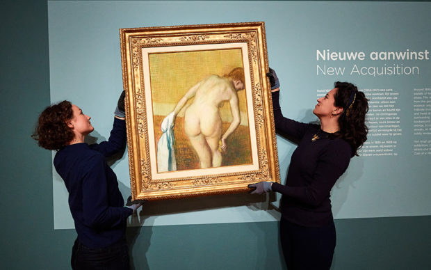 Curator Fleur Roos Rosa de Carvalho puts Woman Bathing by Edgar Degas up on the wall in the Van Gogh Museum, together with an art-handler. Photo: Jan-Kees Steenman