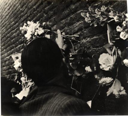 Bologna 25 aprile 1945. La madre di un partigiano caduto depone un fiore davanti a quello che diventerà il Sacrario della Resistenza in Piazza Nettuno. Photo courtesy Istituzione Bologna Musei | Museo civico del Risorgimento