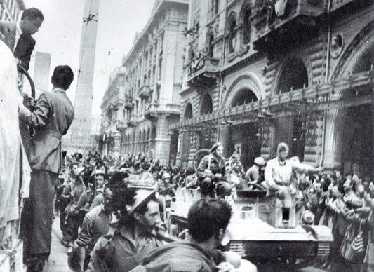 Bersaglieri e truppe alleate sfilano in via Rizzoli. Il generale Clarke sopra il carrarmato saluta la folla festante il 21 aprile 1945. Foto ANPI Bologna