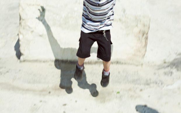 """Lea Anouchinsky, Shalom, Gerusalemme 2011. """"In viaggio, alla ricerca delle mie radici e della storia del mio cognome, ero nella Città Vecchia brulicante di bambini, custodi di accessi preclusi allo sguardo poco attento dei turisti. Il protagonista della foto mi ha sorriso, mi ha invitato a seguirlo. E per soli 2 shekel (50 centesimi) mi ha raccontato la sua libertà: un salto, a cielo aperto, sui tetti del mondo"""""""